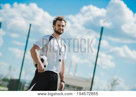 Portrait Of Referee Holding Soccer Ball While Standing On Soccer Pitch