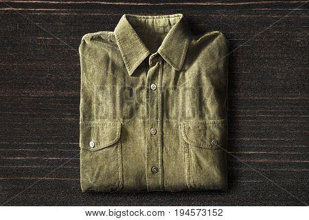 Khaki velveteen shirt folded on dark wooden background