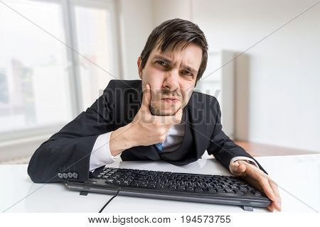 Suspicious Man Is Working With Computer And Looking On Screen.