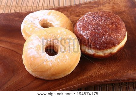 Assorted Homemade Doughnuts with Jelly filled and powdered sugar on wooden salver. Selective focus