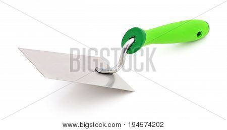 Metal trowel with a green plastc handly on a white background.