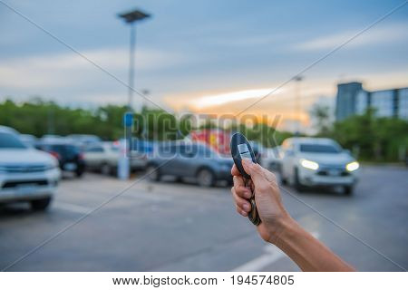 remote control  key Car in hand In the outdoor parking lot at evening  , system automatic.
