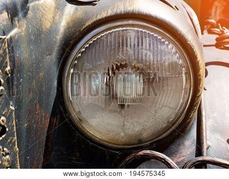 Glass headlight vintage dark car on a Sunny day. The horizontal frame.
