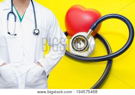 smart doctor with a stethoscope around his neck with red heart and a stethoscope on yellow background heart health care and medical technology concept selective focus.