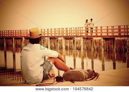 Asian broken heart man looking at lover on bridge Vintage style color Dark tone