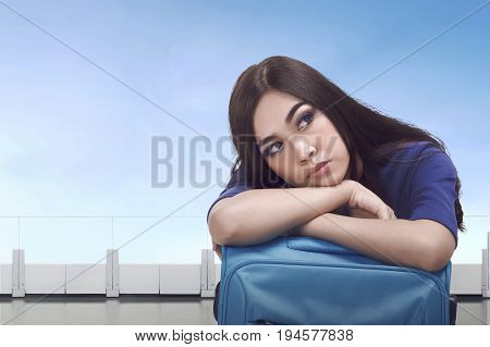Bored Asian Tourist Woman Waiting With Luggage