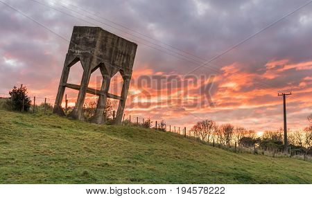 Old water tower leaning over on a hill side with a sunrise cloudy sky.