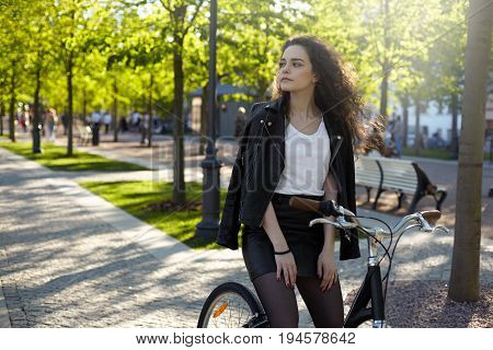 Urban summer shot of cute student girl dressed stylishly in short black skirt and leather jacket over shoulders sitting on bike in park and looking sideways waiting for friend to join her for ride