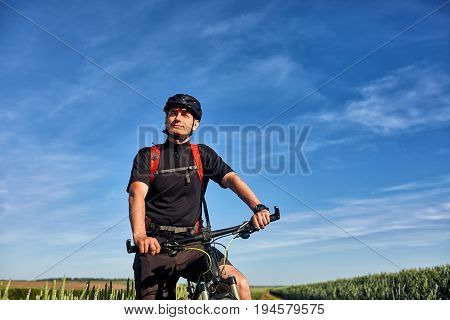 Young cyclist with mountain bicyclist on the path of the field in the countryside against sunrise. Sportsman dressed in the sportwear, with helmet, sunglasses and red backpack. Beautiful landscape like a background. Concept of the healthy lifestyle.