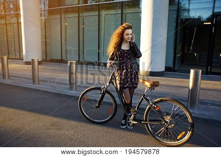 Cute teenage girl wearing stylish clothing standing on desert street with her vintage bike and talking on mobile phone. Pretty woman making stop answer phone call while riding bicycle on city streets