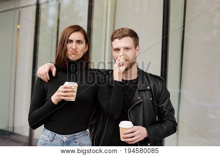People relationships and urban lifestyle. Crazy young couple enjoying nice time together making faces drinking fresh takeaway coffee out of papercups while having morning walk on city streets