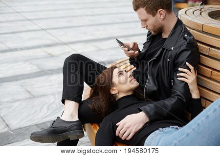 Modern technology internet addiction and relationships. Stylish hipster sitting on bench outdoors busy using web-enabled mobile phone ignoring his pretty girlfriend who is lying on his lap