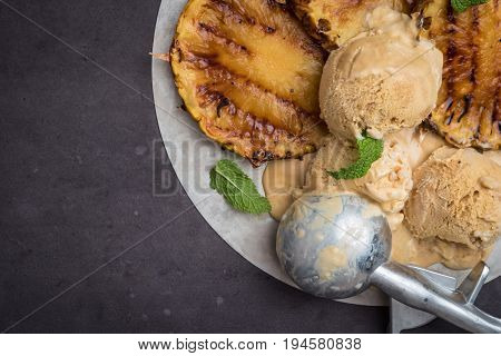 Grilled pineapple with vanilla ice cream and mint leaves