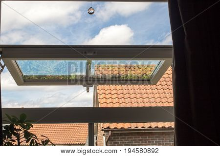 Urban living. View from open UPVC window reflecting garden on modern urban housing estate. Blue cloudy sky and roof tops visible through house window on hot day.