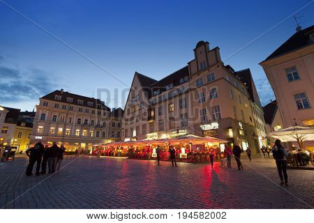 TALLINN ESTONIA- SEPTEMBER 5 2015 A crowd of tourists visit evening Town hall square in the Old city on September 5 2015 in Tallinn Estonia.