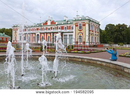 TALLINN ESTONIA- SEPTEMBER 7 2015: tourist photographs the Kardiorg palace at Kadriorg Park on phone in Tallinn Estonia.