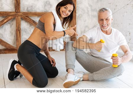 Great result. Handsome smiling man wearing sport clothes and holding dumbbells while looking straight at camera