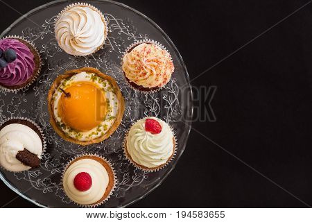 Top view on homemade vanilla blueberyy lemon chocolate cupcakes on cristal plate on black wooden background. Healthy food snack for birthday party or celebration