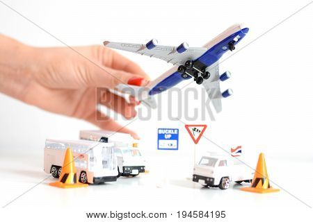Travel concept with woman hand holding airplane toy above airport infrastructure