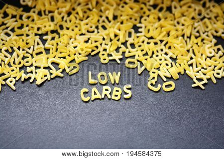 Low carbs phrase spelled with raw letter-shaped pasta on blackboard background