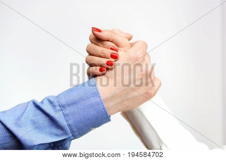 Business man and business woman shaking hands suggesting gender equality at the office
