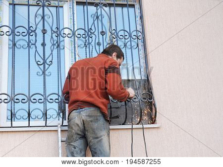 KYIV UKRAINE - JULY 11 2017:  Worker install window iron security bars for house safety. Contractor installing window iron security bars with welding. Security Shutters Grilles Installation.