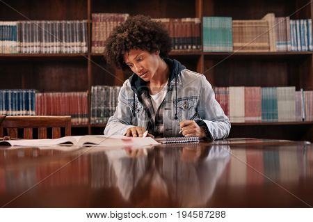 Young Student Making Notes From Books In Library
