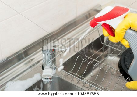 Housemaid With Disinfecting Spray In The Kitchen