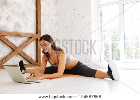 Watching video. Charming sportswoman keeping smile on her face and leaning on elbows while stretching legs