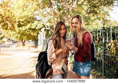 Beautiful college students looking at pictures on mobile phone. Young women with book looking at smart phone.