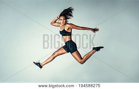 Female Model In Sports Wear Jumping In Air
