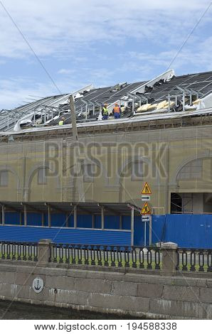 Builders assemble the roof of the building in the summer under the blue sky on the canal