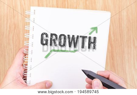 Growth Word On White Ring Binder Notebook With Hand Holding Pencil On Wood Table,business Concept