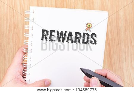 Rewards Word On White Ring Binder Notebook With Hand Holding Pencil On Wood Table,business Concept.