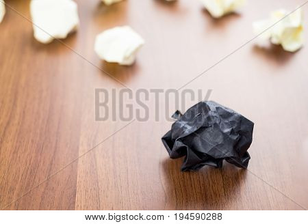 Black Crumpled Paper Ball On Dark Brown Wood Table With Group Of White Crumpled Paper Ball At Backgr