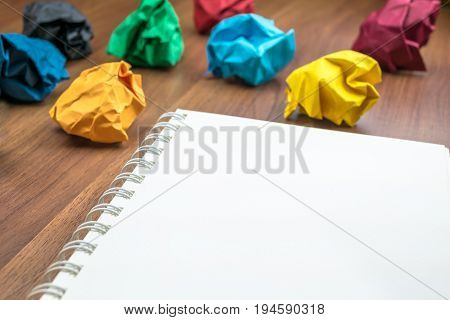 Open Blank Ring Binder White Book  With Group Of Colorful Crumpled Paper Ball On Dark Brown Table To
