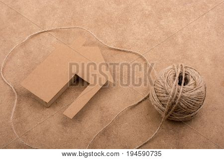 House Shape Cut Out Of Paper And Spool Of Thread