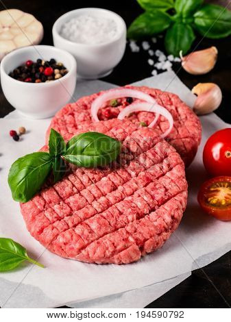 Close Up View Of Two Raw Meat Steak Cutlets For Burger With Vegetables