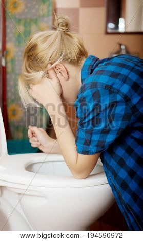 Sick young woman leaning on open toilet seat.