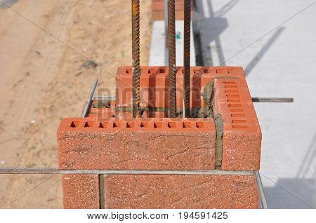 Bricklaying construction. Installing Red Clinker Blocks and Caulking Brick Masonry Joints Exterior Brick Column with Iron Rod.