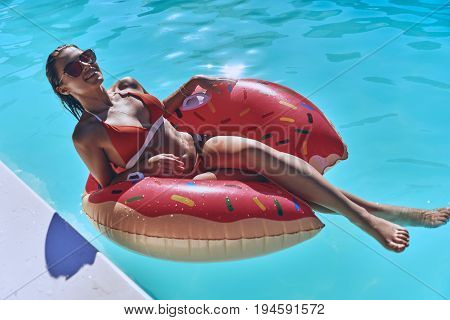 Let the worries float away. Attractive young woman in swimwear smiling while floating on the inflatable ring in the pool