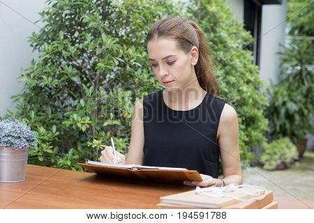 Portrait of a beautiful young woman reading book while driking coffee 20-30 year old.