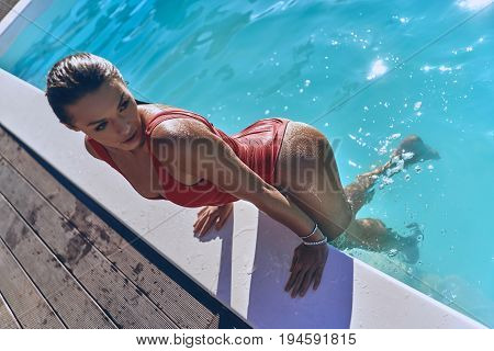 Supremely sensual. Top view of attractive young woman in swimwear looking away while getting out the swimming pool