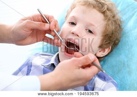 Close up of boy having his teeth examined by a dentist.