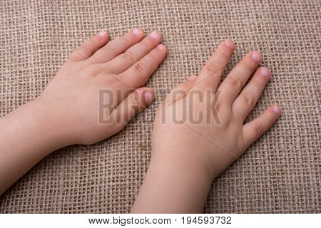 Toddler hand with canvas linen background under it