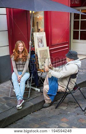 PARIS FRANCE - JUNE 6 2012: An unidentified model has her portrait drawn by an unidentified artist in Montmarte in Paris.