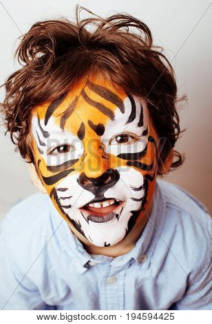little cute boy with faceart on birthday party close up, little cute orange tiger