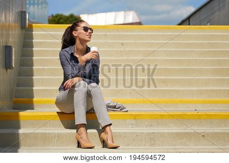 Business woman siting and  drinking coffee. Lawyer professional or similar walking outdoors happy holding disposable paper cup.