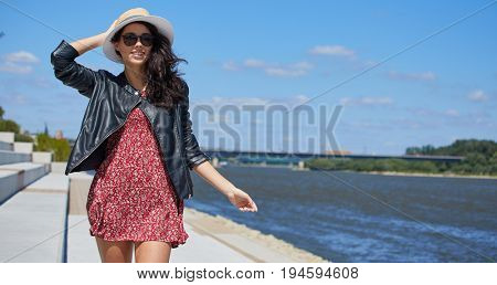 A woman is walking on the riverbank in the city on a sunny day
