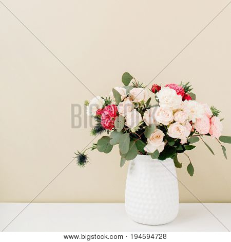 Beautiful flowers bouquet in flowerpot in front of pale pastel beige wall. Floral lifestyle composition.